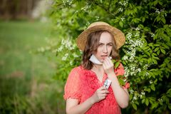 Young girl blowing nose and sneezing in tissue in front of blooming tree. Seasonal allergens affecting people. Beautiful lady has. Rhinitis royalty free stock image
