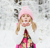 Young girl blowing snow. In winter forest Royalty Free Stock Photo