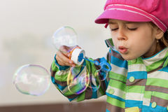 Young girl blowing soap bubbles Stock Images