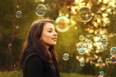 Young girl blowing soap bubbles. Stock Photo