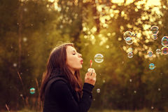 Young girl blowing soap bubbles. Royalty Free Stock Photos