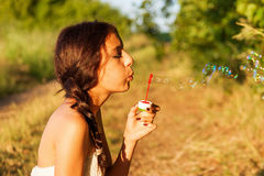 Young girl blowing soap bubbles Royalty Free Stock Images