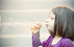 Young girl blowing soap bubbles Royalty Free Stock Photography