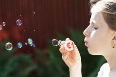 Young girl blowing soap bubbles Stock Photo