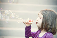 Young girl blowing soap bubbles Royalty Free Stock Photos