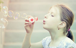 Young girl blowing soap bubbles Royalty Free Stock Image