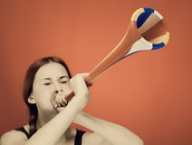 Young girl blowing trumpet over red background Royalty Free Stock Photos