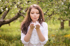 Young girl blows off petals Stock Images