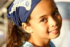 A young girl in blue bandanna. Enjoying the evening sun Stock Images