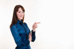 Young girl in a blue blouse pointing at empty space on left Stock Photography