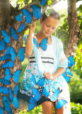 Young girl with blue butterflies Stock Images