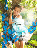 Young girl with blue butterflies Stock Photography