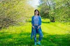 Young girl in blue clothes at garden. Royalty Free Stock Photos