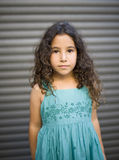 Young girl in blue dress. In front of a garage door Stock Photos