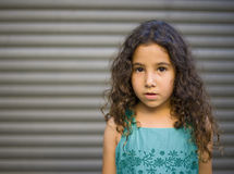 Young girl in blue dress. In front of a garage door Royalty Free Stock Images