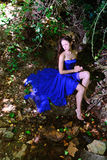 A young girl in a blue dress at the creek Royalty Free Stock Photo