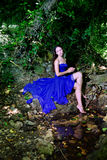 A young girl in a blue dress at the creek Royalty Free Stock Photography