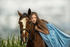 Young girl in a blue dress on a horse Stock Images