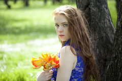 Young girl in a blue dress relaxing in spring park Stock Image