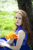 Young girl in a blue dress relaxing in spring park Royalty Free Stock Photography