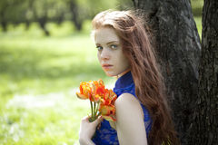 Young girl in a blue dress relaxing in spring park Royalty Free Stock Photos