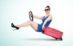 Young girl in blue dress and sunglasses with steering wheel goes on a cruise. Travel by car concept stock image