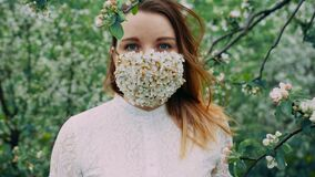 Young girl with blue eyes in the flower mask in the cherry orchard.