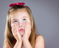 A young girl with blue eyes. Little girl with blue eyes, put her hands on her cheeks Royalty Free Stock Images