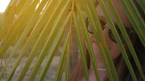 Young girl in blue hat and glasses looks at tropical palms. Close Up Shot. stock footage