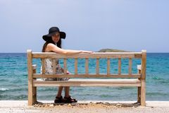 A young girl in a blue hat sitting on a wooden bench on the shore of the Mediterranean sea on the island of Crete. A young woman in a blue hat sitting on a Stock Photography