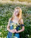 The young girl in a blue jeans sundress with a bouquet of wild flowers Royalty Free Stock Images