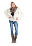 Young girl with blue jeans, winter jacket and boots standing pos. Ing over white background Royalty Free Stock Images