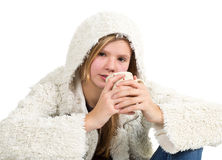 Young girl with blue jeans and winter jacket sitting, holding cu Royalty Free Stock Image