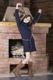 Young girl in blue jersey near fireplace Stock Photography
