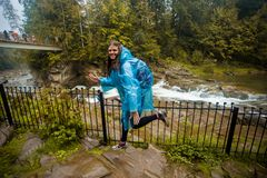 Young girl in blue raincoat stands in rain royalty free stock images