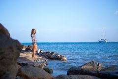 Young girl on blue sea background. Tropical country. Yacht on the background.  Royalty Free Stock Image