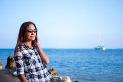 Young girl on blue sea background. Tropical country. Yacht on the background.  Stock Images