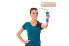A young girl in the blue shirt raised up roller for painting walls Stock Image