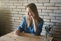 Young girl in blue shirt sits at table in headphones and thought. Young blond girl in blue shirt sits at table in headphones and thoughtfully bowing her head Royalty Free Stock Image