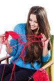 Young girl in a blue sweater sits on a chair with a red ball of yarn and knitting a scarf and Spitz. Smiles. White background. Royalty Free Stock Image