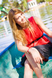 Girl sunbathing. Portrait of a young girl smiling in the boat in park Royalty Free Stock Photo