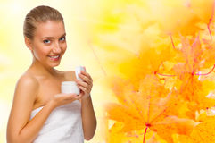 Young girl with body cream on autumnal background Stock Images