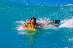 Young girl body surfing in Waikiki Beach Hawaii. Oahu, Hawaii - May 25, 2015: Young girl surfing on a boogie board in Hawaii in Waikiki Beach Stock Photo