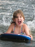 Young girl on boogie board. Young girl screaming and splashing in the lake on a boogie board Royalty Free Stock Photos
