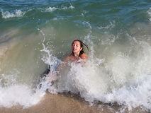 Young Girl Boogie Boarding. A young girl riding a wave on a boogie board Stock Image