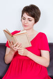 Young girl with book on brown sofa Stock Photography