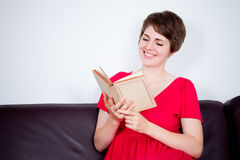 Young girl with book on brown sofa Royalty Free Stock Photography