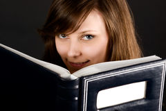 Young girl and book in dark. Young girl looks out from book in dark colours Stock Images