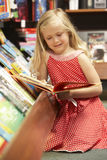 Young girl in bookshop Stock Photos