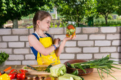 Young girl bottling a variety of vegetables stock photos